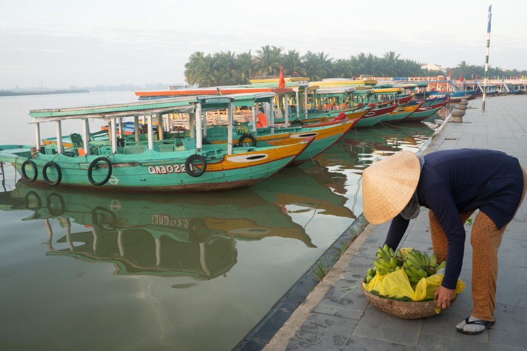 Fruit seller and longboats in Hoi An