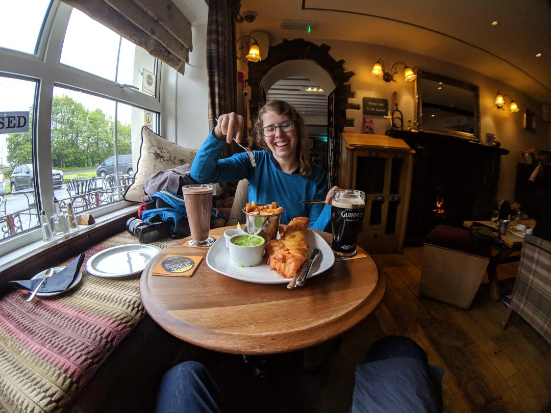 Woman eating traditional fish and chips in English countryside tavern