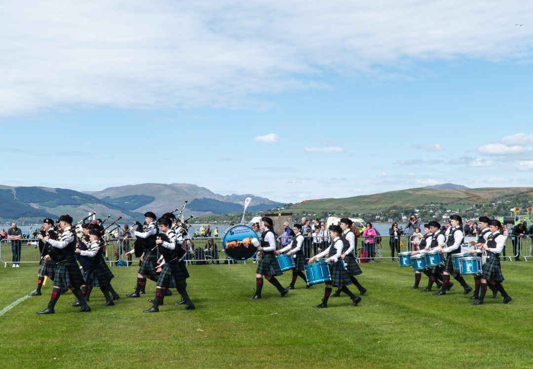 Scottish pipe band marching onto field at highland games