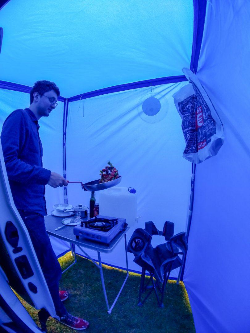 Man cooking inside campervan rain shelter