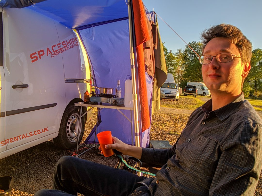 Man relaxing with campervan and drink in hand