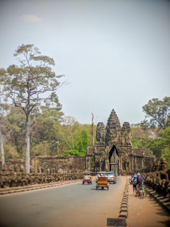 Tuk Tuks driving over bridge to Angkor Thom.