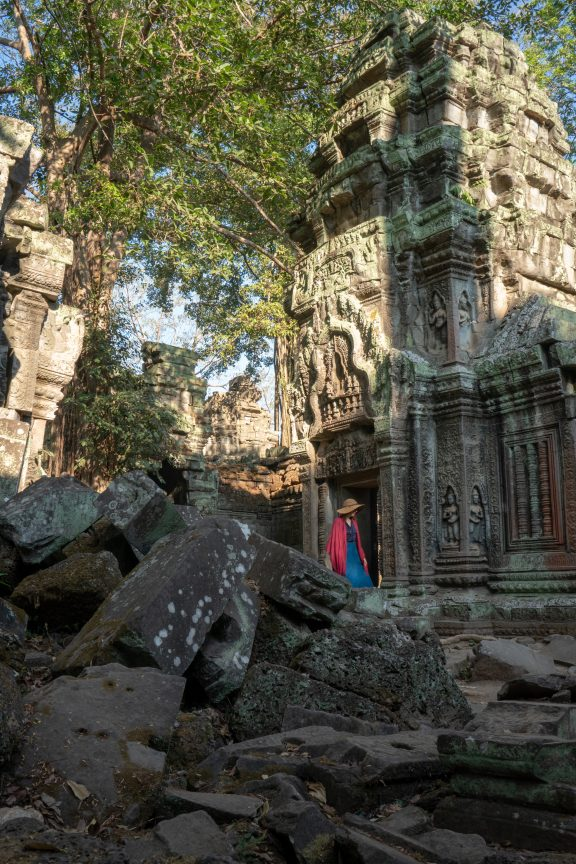 Woman exploring Ta Prohm Tomb Raider temple