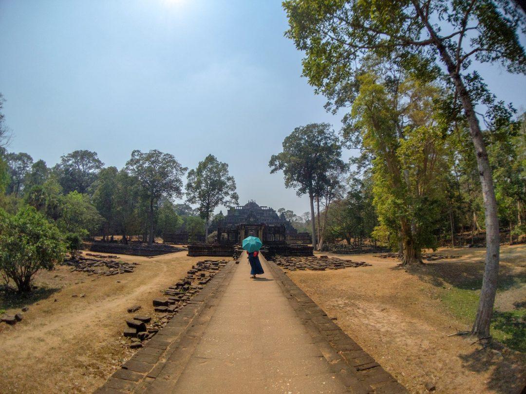 Woman walking along stone bridge to Baphuon Temple.