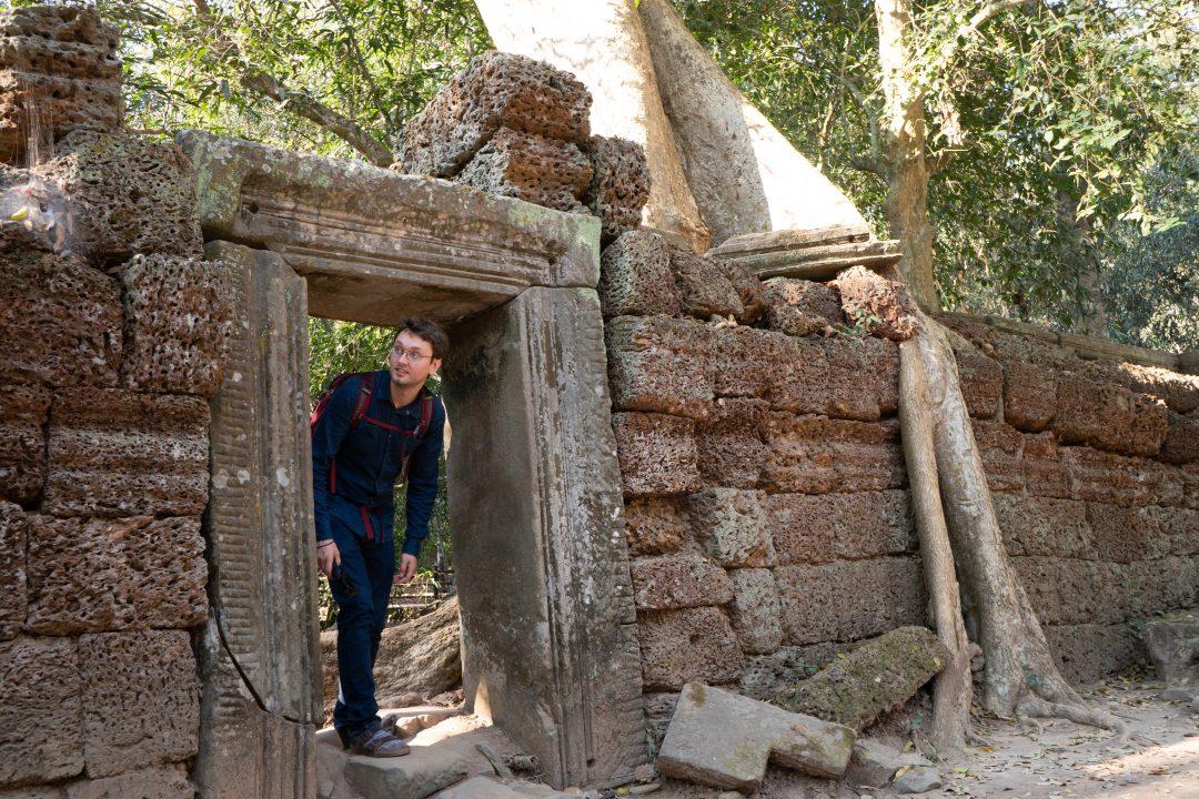 Man exploring Ta Prohm Tomb Raider temple