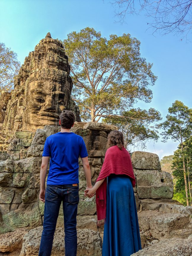 Couple standing at the Victory Gate in Angkor Wat temple complex.
