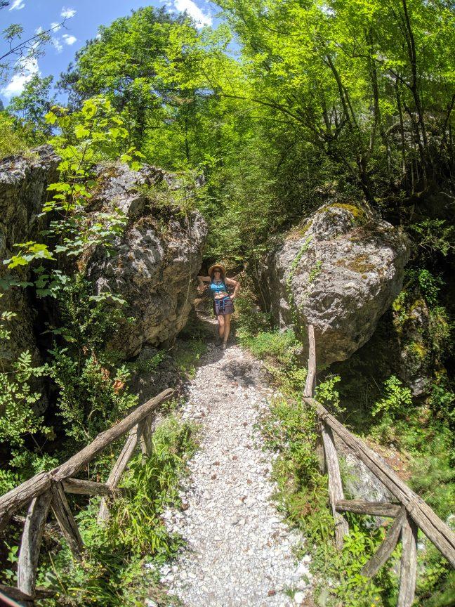 Woman standing near big rock on E4 Olympus trail in Greece