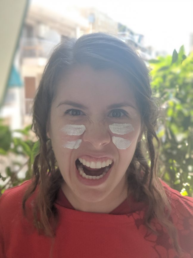 Woman with sunscreen on face to prevent sunburn.