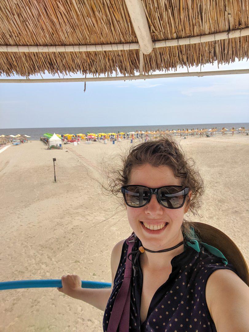 Woman standing under sun hut at beach