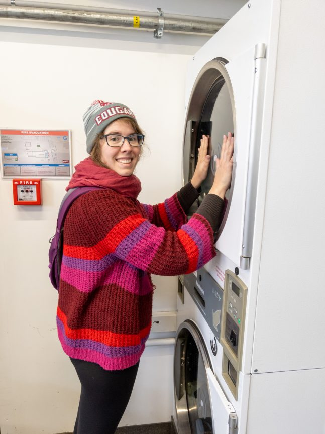 Woman warming hands up on laundry machine
