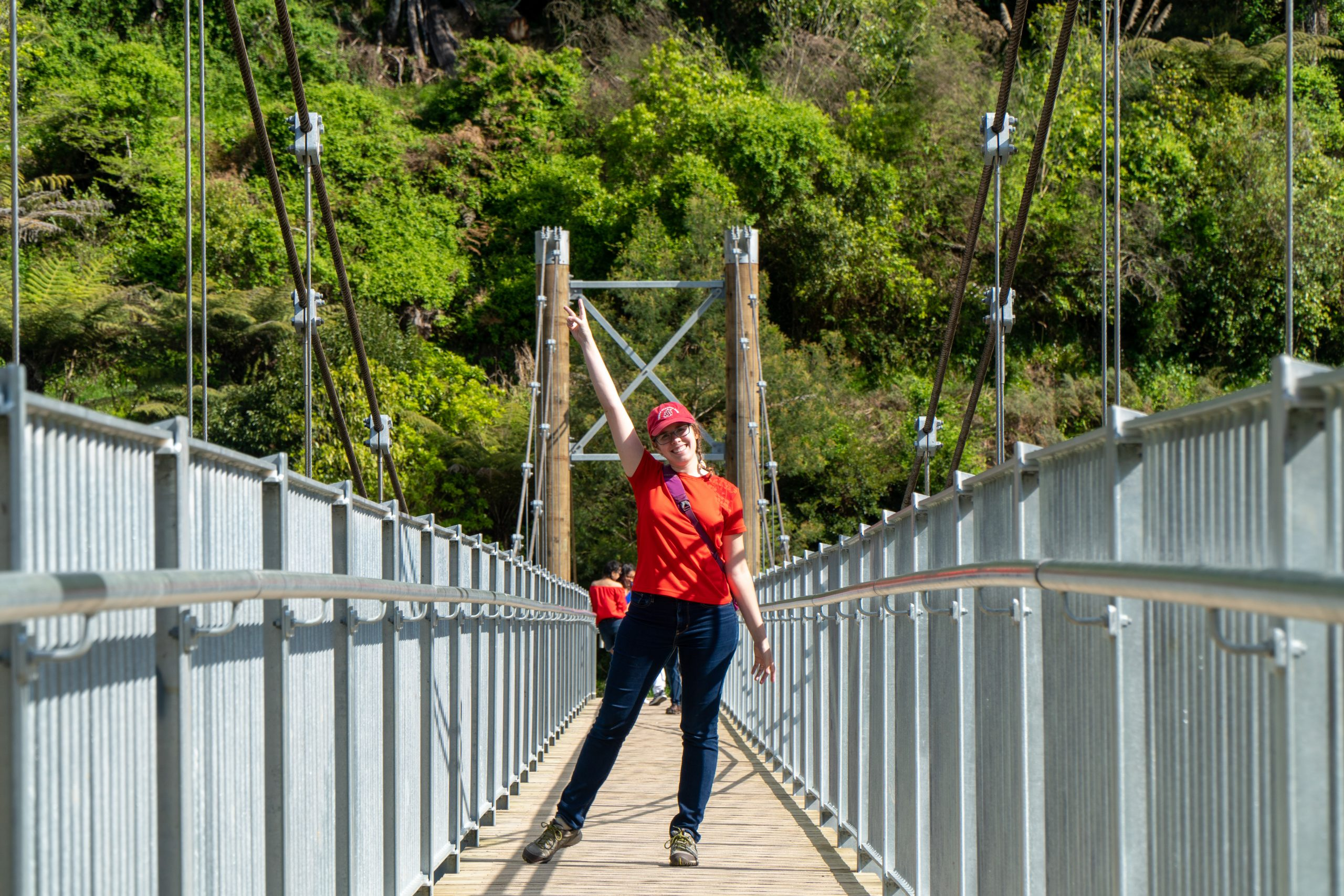 Woman standing on suspension bridge in New Zealand.