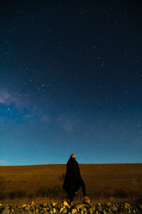 Woman standing alone gazing up aDark Sky in New Zealand