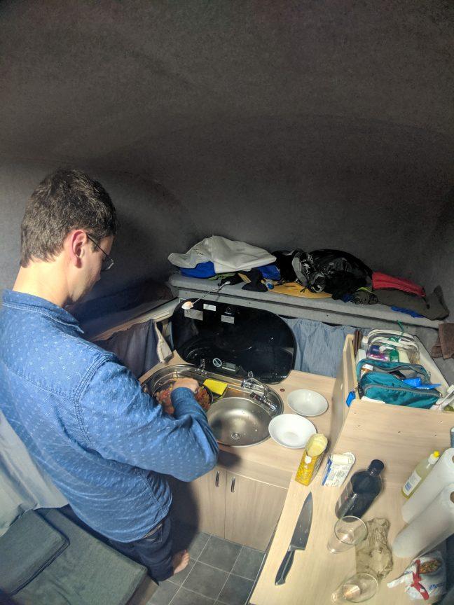 Tall man standing inside campervan.
