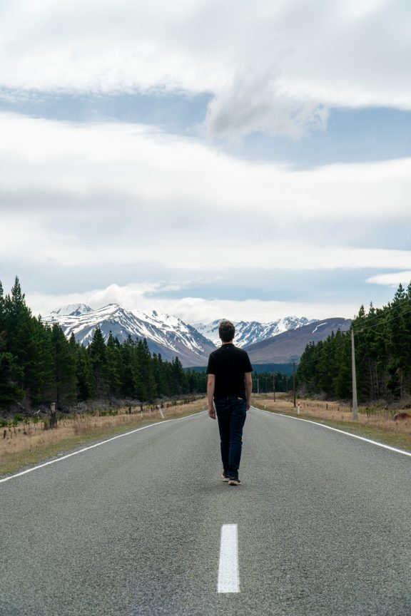 Man walking down Mount Cook Road. Hitchhiking best way to see New Zealand.