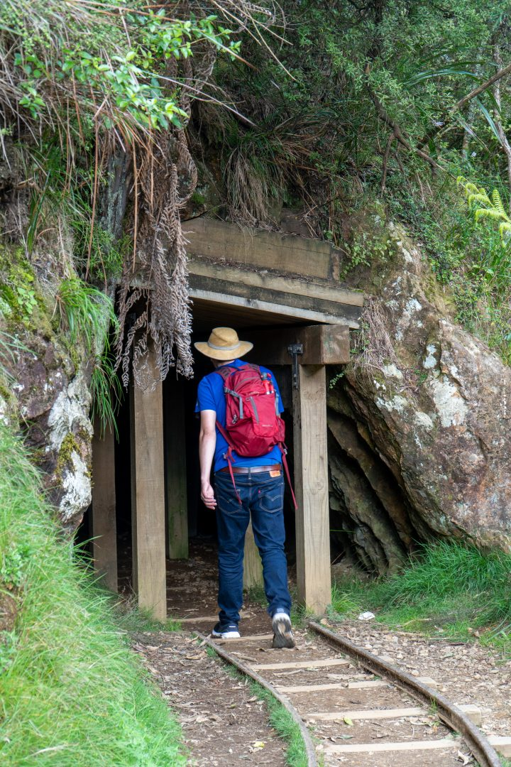 Man walking into old mining tunnel.