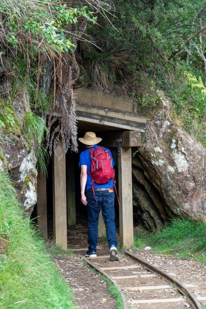 Man walking into old mining tunnel.