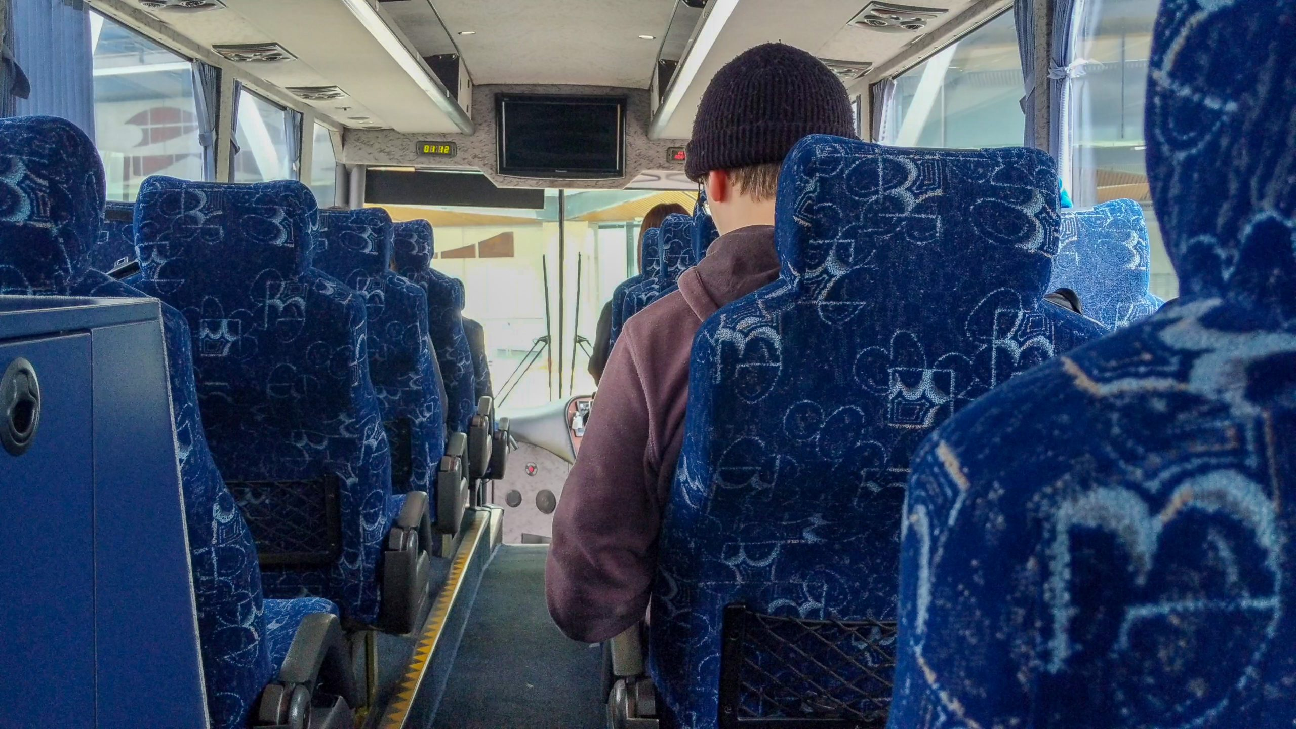 man looking down at phone while on bus