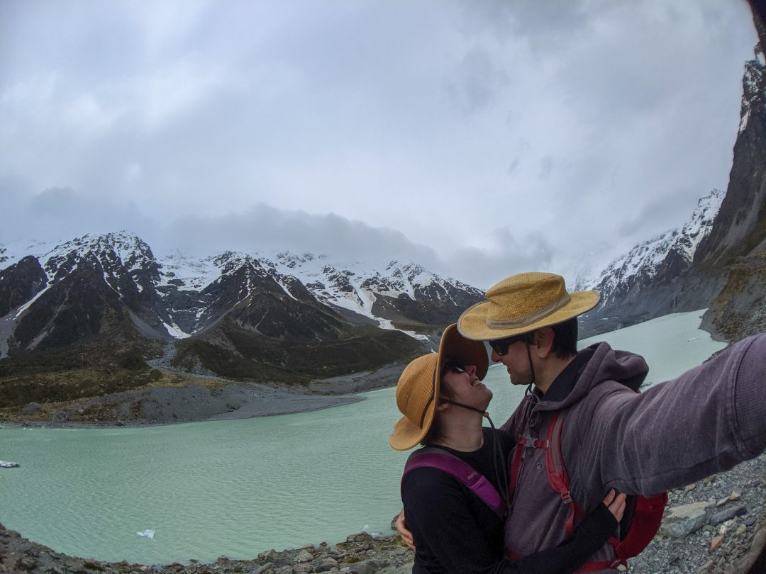 Couple holding each other at Hooker Lake in New Zealand