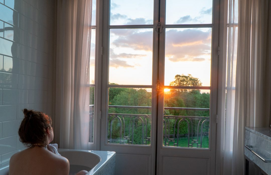 Woman in bath watching sunset